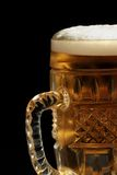Beer mug. Full beer mug with foam on the dark background Stock Images