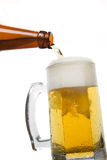 Beer mug. Beer bein poured from the bottle isolated on white Royalty Free Stock Images
