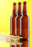 Beer mug and bottles on yellow background Royalty Free Stock Photography
