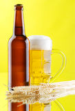 Beer mug and bottles on yellow background Royalty Free Stock Image