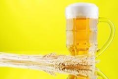 Beer mug and bottles on yellow background Stock Image