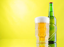 Beer mug and bottles on yellow background Royalty Free Stock Photos