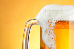 Beer mug with froth. Over yellow background stock photo