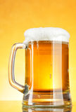 Beer mug with froth. Over yellow background royalty free stock photos
