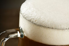 Beer mug with froth. Over dark background stock photography