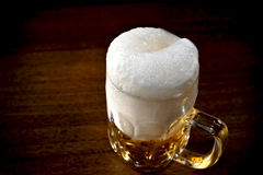 Beer. Mug full of beer with froth on the wooden table Royalty Free Stock Images