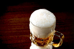 Beer. Mug full of beer with froth on the wooden table Royalty Free Stock Photos