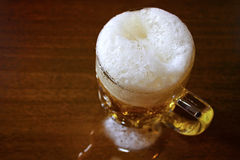 Beer. Mug full of beer with froth on the wooden table Stock Photo