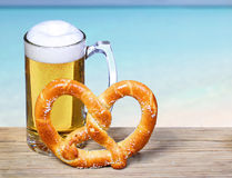 Beer Mug with German Pretzel over Ocean view. Stock Photo