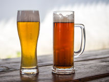 Beer mug and glass with light or dark drinks. Two different beer drings in a beer mug and glass, light and dark, barley and wheat Royalty Free Stock Photo