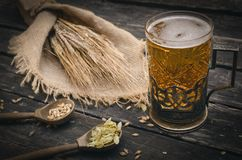 Glass of frothy beer, malt and hop. Beer in the mug glass with malt and hop and rye ears on the aged wooden table background stock photos