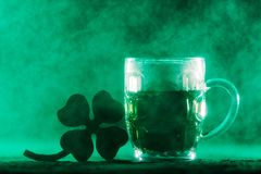 Beer mug with green beer and shamrock in a smoke. Beer mug with green beer in it and a four-leaf clover in a green smoke. Irish culture. St. Patrick`s Day Stock Photography