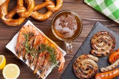 Beer mug, grilled shrimps, sausages and pretzel. On wooden table. Top view stock image