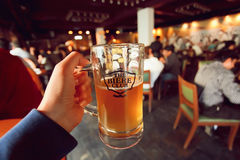 Beer mug in hand of visitor of the popular Biere Brewing Company and Club Royalty Free Stock Image