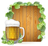 Beer mug and hops on a wooden background Royalty Free Stock Photography