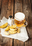 Beer mug and potato wedges on rustic wood table Royalty Free Stock Photography