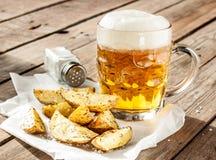 Beer mug and potato wedges on wood table Stock Photography