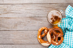 Beer mug and pretzel on wooden table Royalty Free Stock Photos