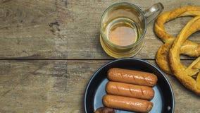 Beer mug, pretzels, and sausages. Beer mug, pretzels, and fried sausages on wooden table Stock Image