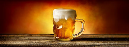 Beer in mug on table. Light beer in glass mug on wooden table Stock Photo