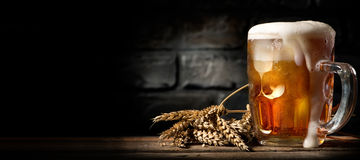 Beer in mug on table. Beer in mug on wooden table near brick wall stock photography