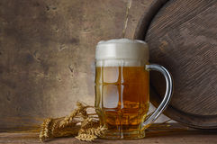 Beer mug with wheat ears and wooden barrel on a dark wall background, pour beer Royalty Free Stock Image