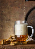 Beer mug with wheat ears and wooden barrel on a dark wall background, pour beer Stock Photo