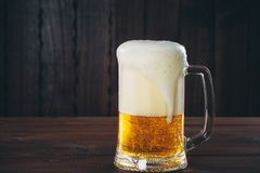 Beer. Mug of beer on the wooden background. Beautiful background of the Oktoberfest Royalty Free Stock Image