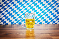 Beer mug on wooden board in front of bavarian flag Royalty Free Stock Photos