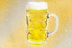 Beer mug on yellow background Drop. Stock Photography