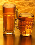 Beer mugs. With froth over yellow background Stock Images