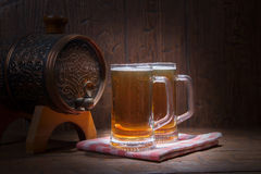 Beer mugs and barrel on a wooden background Royalty Free Stock Photography
