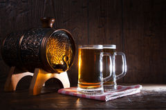 Beer mugs and barrel on a wooden background Royalty Free Stock Images
