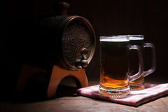 Beer mugs and barrel on a wooden background Royalty Free Stock Image