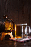 Beer mugs and barrel on a wooden background Stock Image