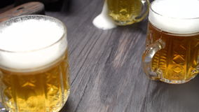 Beer mugs on black bar counter stock video