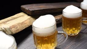 Beer mugs on black bar counter stock video footage