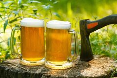 Beer mugs cheers. Picnic party on natural background with axe Royalty Free Stock Images