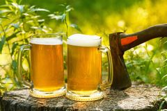 Beer mugs cheers on natural background. Beer mugs cheers, picnic or party on natural background with axe Royalty Free Stock Image