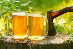 Beer mugs cheers on natural background. Beer mugs cheers, picnic or party on natural background with axe Stock Image