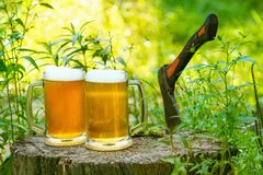 Beer mugs cheers on natural background. Beer mugs cheers, picnic or party on natural background with axe Stock Photography