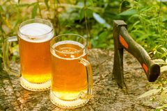 Beer mugs cheers on natural background. Beer mugs cheers, picnic or party on natural background with axe, top view Stock Photos