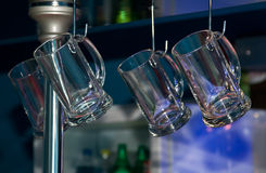 Beer mugs hanging in a bar Stock Image