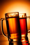 Beer mugs over yellow background Royalty Free Stock Photo