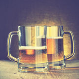 Beer mugs. On the wooden table. Retro style filtred Royalty Free Stock Photography