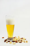 Beer and munchies. Glass of beer, popcorn and almonds with a white background Stock Photos