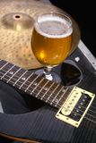 Beer and music equipment. Glass full of light beer standing on a case with some music equipment Royalty Free Stock Images