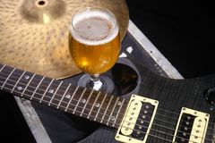 Beer and music equipment. Glass full of light beer standing on a case with some music equipment Royalty Free Stock Image