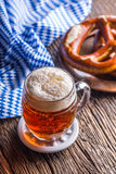 Beer and Oktoberfest. Draft beer pretzel and blue checkered tablecloth as traditional products for bavarian festival oktoberfest.  Royalty Free Stock Photos