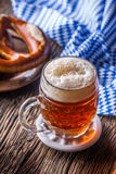 Beer and Oktoberfest. Draft beer pretzel and blue checkered tablecloth as traditional products for bavarian festival oktoberfest.  Royalty Free Stock Photography